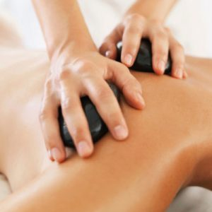 South Africa, Cape Town, Woman relaxing while getting stone massage